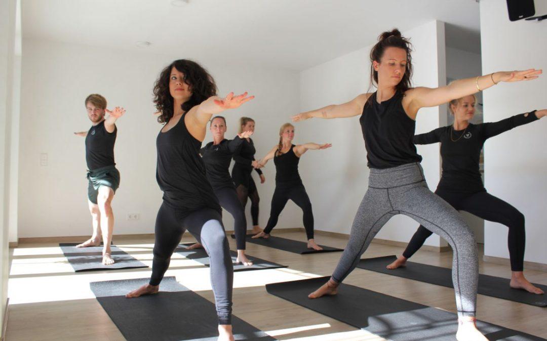 Gruppe übt Yoga als Prävention