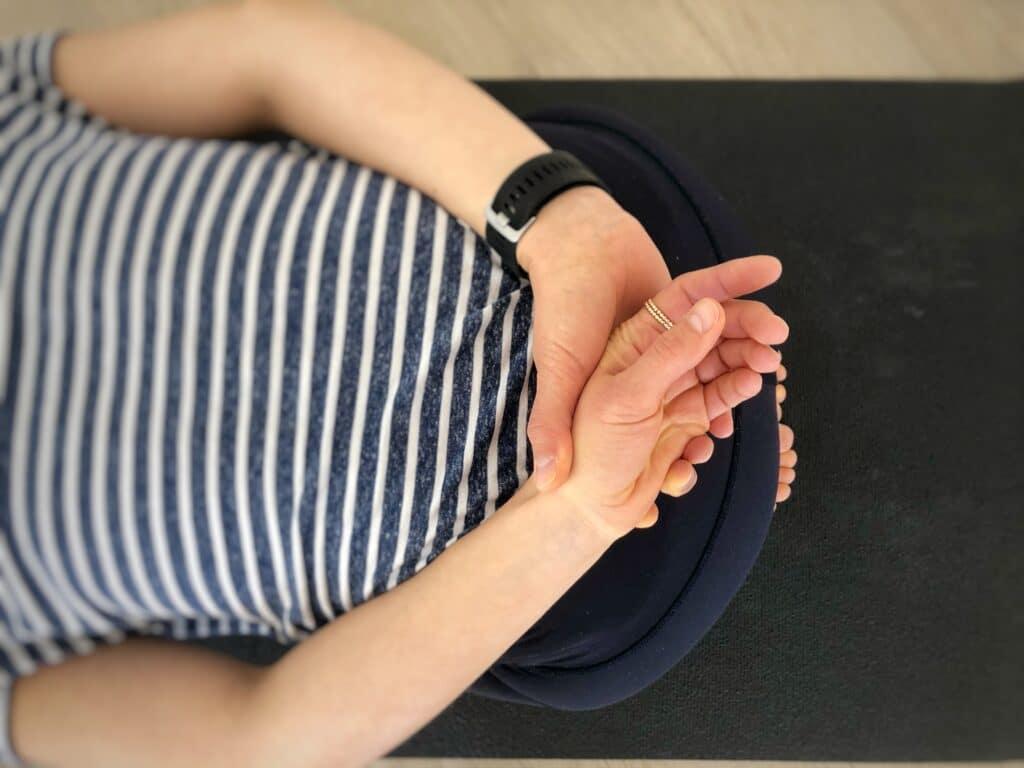 Hände auf dem Rücken verschränkt in der Kindeshaltung